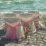 Rental chairs with covers at Anna Maria Island beach wedding ceremony